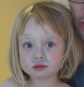 Child's face with green marker stains