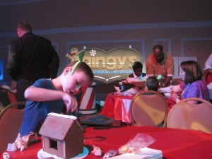 Boy decorating a gingerbread house