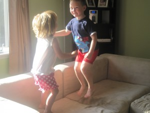 Two children jumping on a sofa