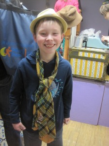 Boy in dressing-up hat and tie.